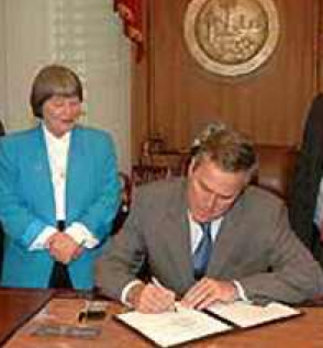 "NRA lobbyist, Marion Hammer, watches Jeb Bush sign Florida's ""Stand Your Ground"" law in 2005"